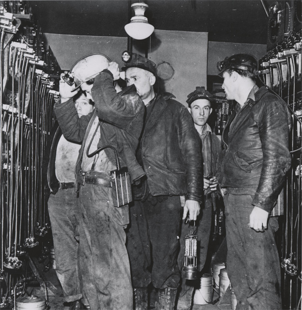 Image of Miners wearing helemts with Edison Cap Lamps
