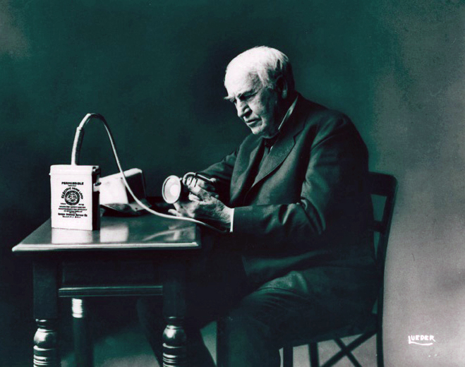 Image of Thomas Edison with his battery powered cap lamp