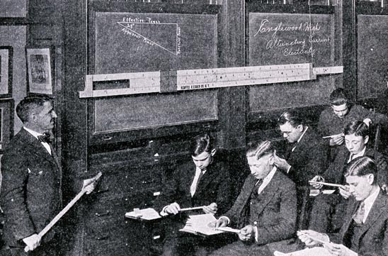 Image of a teacher and class with individual and demonstration slide rules